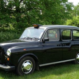 taxi anglais noir sur herbe prise de vue en trois quart avant gauche
