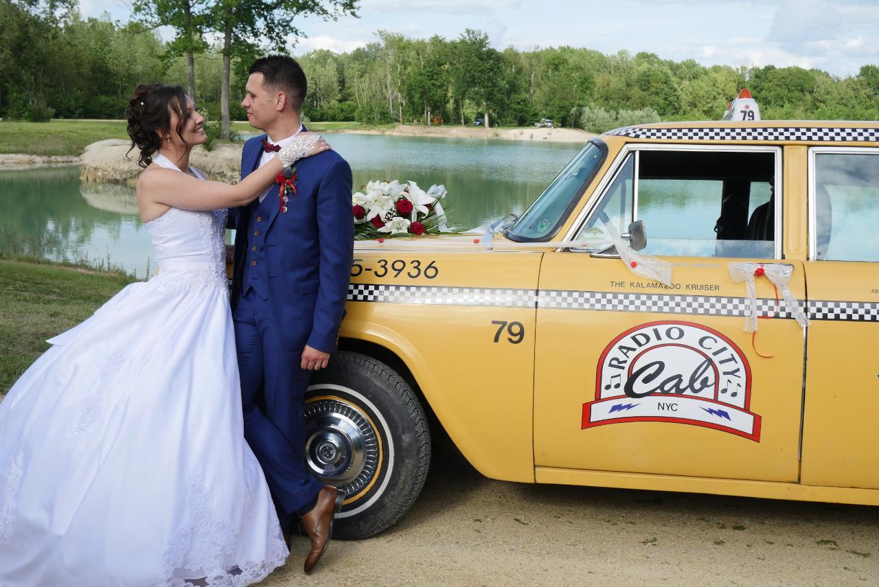 les mariés avec leur taxi new-yorkais decores en rubans et fleurs