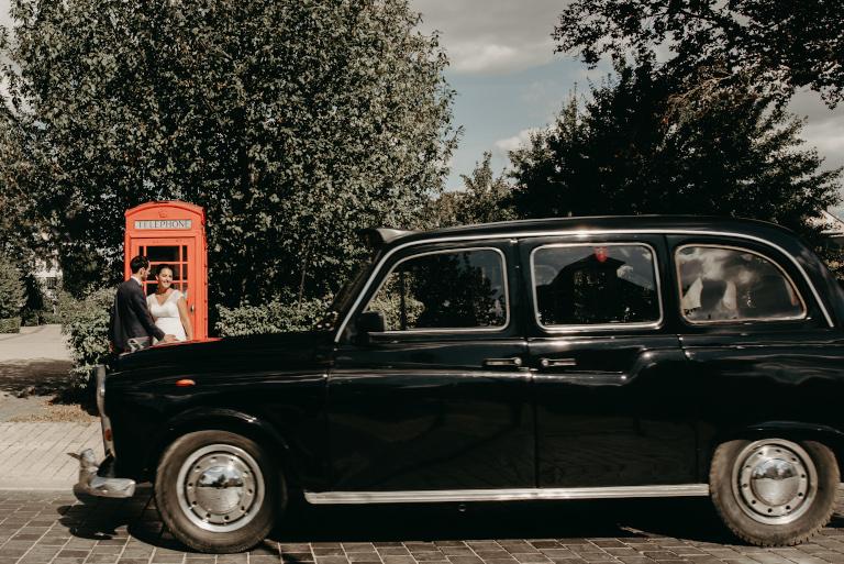 taxi anglais noir devant cabine telephonique rouge et les maries