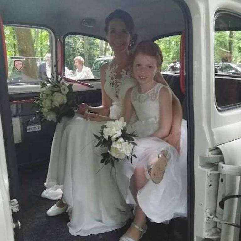 la mariee et enfant d'honneur dans taxi anglais blanc