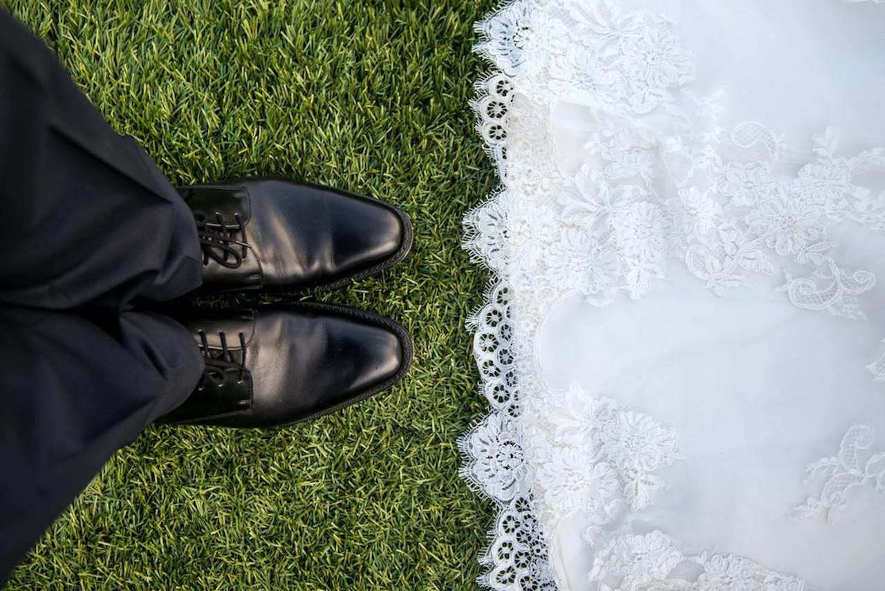 les maries debout en face a face detail chaussures noirs et bas de robe de mariee