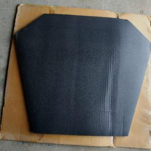 photo prise d'une plaque de mousse recouverte de plastique noir sur un carton marron sur sol en beton d'un isolant thermique capot insonorisant moteur taxis anglais