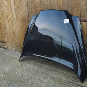 capot noir taxi anglais pose contre porte garage en bois sur sol en beton