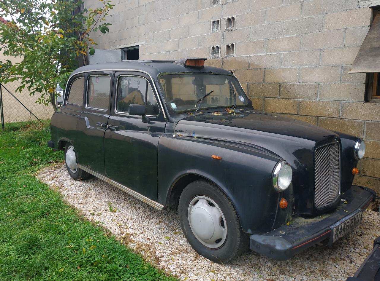 taxi anglais noir fairway devant un mur en parepaings